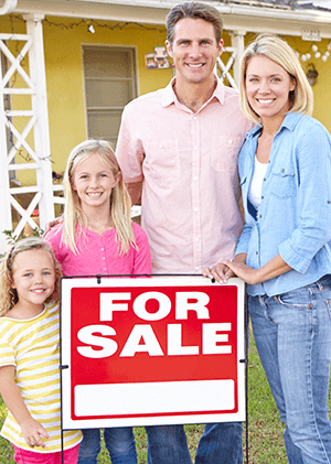 family in front of their house with a for sale sig